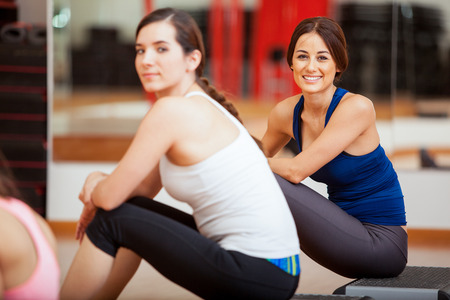 Cute young female friends taking a break from a class at a gym photo