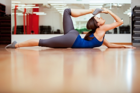 Pretty young woman stretching and getting ready for her yoga class