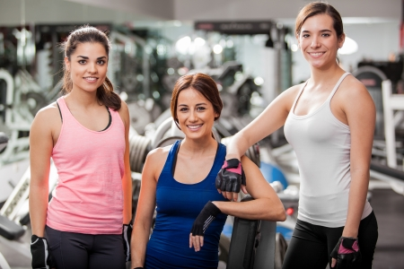 Group of cute young women taking a break from their workout at the gym photo