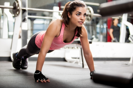 women health: Gorgeous brunette riscaldamento e facendo alcune push up una la palestra