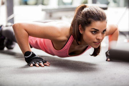 Beautiful Latin woman doing push ups in the gym before lifting some weights Stock Photo