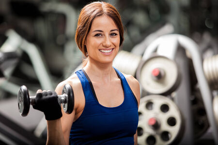 curls: Happy young brunette doing some bicep curls with dumbbells and smiling in a gym