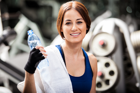 Beautiful Latin woman resting and drinking some water after a workout at the gym