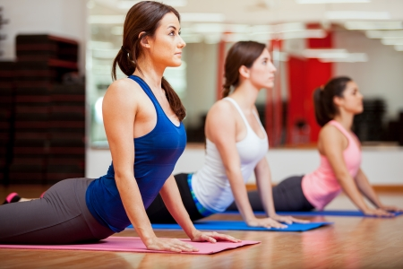 female pose: Cute Hispanic women practicing the cobra pose during their yoga class in a gym