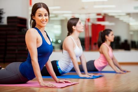 fitness training: Mooie jonge vrouw die probeert de cobra pose en glimlachen tijdens yogales Stockfoto