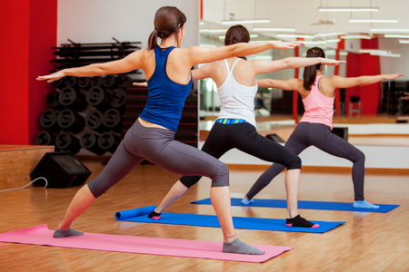 indoors: Group of young women practicing the warrior yoga pose during a class in a gym Stock Photo