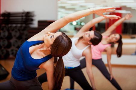 Cute young women practicing the extended side angle yoga pose during a class Stock Photo