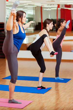 big toe: Cute young women trying out a new yoga pose during a class in a gym Stock Photo