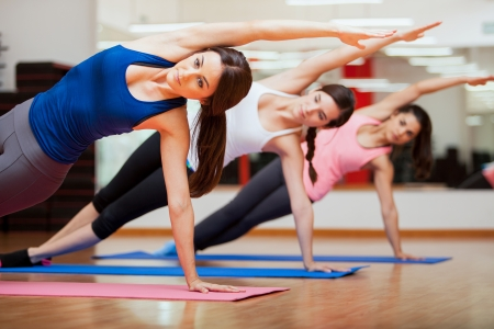indoors: Beautiful group of women practicing the side plank yoga pose during a class in a gym
