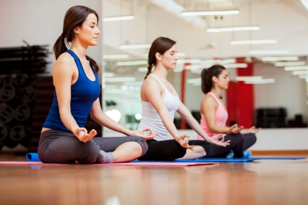 Pretty young women relaxing and meditating in their yoga class at a gym