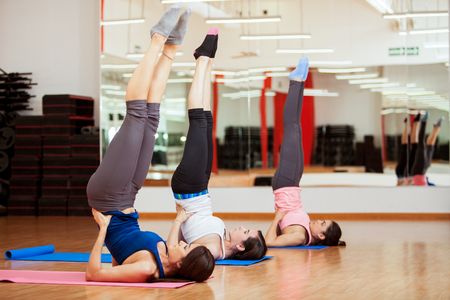 Three pretty young women practicing the shoulderstand yoga pose in a gym Stock Photo