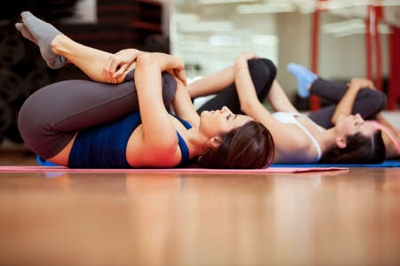 indoors: Group of young women stretching and warming up for a gym class Stock Photo