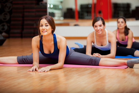 well being: Group of women working on their flexibility and doing some leg splits in a gym