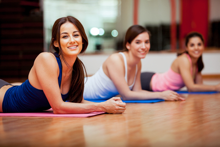 yoga girl: Group of beautiful female friends taking a break from their gym class and smiling