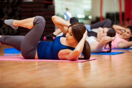 Beautiful young women doing crunches during a class at a gym Imagens