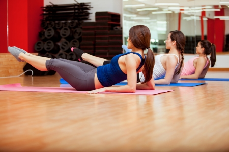 strengthen: Pretty young women doing some crunches to strengthen their core at a gym