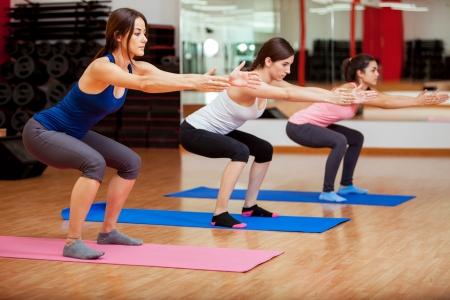 세 아름 다운 젊은 여성 몇 웅크 리고 있기 때문 이라오을하고 헬스 클럽에서 운동