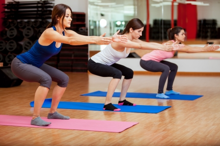 squats: Three beautiful young women doing some squats and exercising at a gym