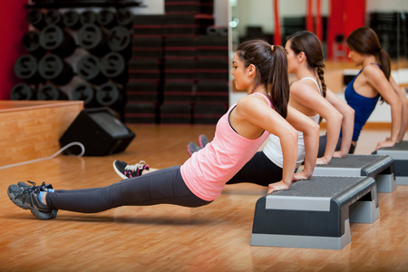 girl in sportswear: Group of cute female Hispanic friends exercising together during a gym class