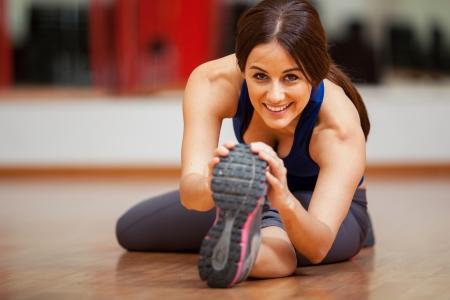 persona feliz: Hermosa morena joven que hace algunos ejercicios de estiramiento y sonriente Foto de archivo