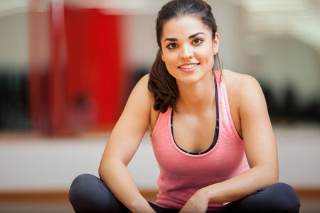 Beautiful young woman sitting down and relaxing at a gym photo