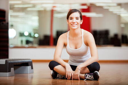 Happy young woman sitting at a gym and preparing for a class photo