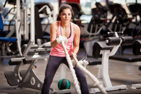 Pretty Hispanic young woman doing some crossfit exercises with a rope at a gym photo