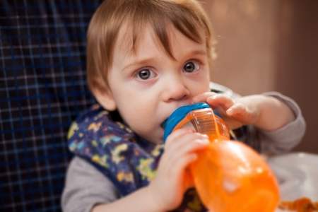 Cute little boy sitting on his chair and drinking water from a bottle