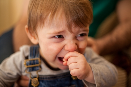 niño llorando: Bebé lindo actuando muy molesto y llorando delante de su padre Foto de archivo