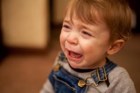 愛らしい小さな白人男の子リビング ルームで泣いています。