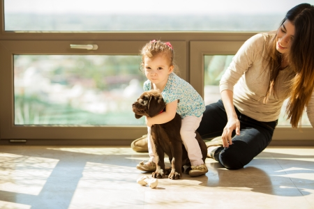 latin family: Cute little Hispanic girl giving his puppy a big hug while hanging out with her mom in the living room