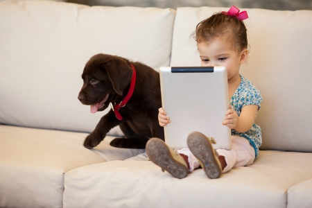 Cute little girl watching a movie on her tablet computer while her dog keeps her company photo