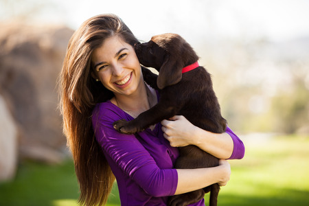 Happy young woman hugging and having fun with her Labrador puppy outdoors