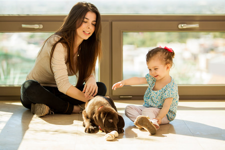 Young mother and her daughter playing and hanging out with their new puppy at home photo
