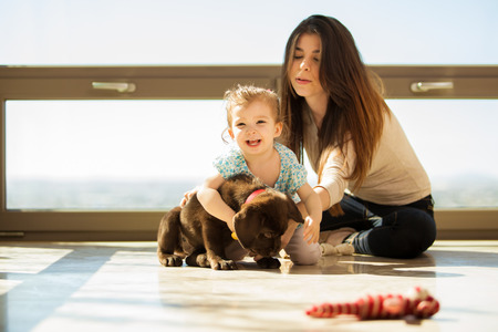 latin family: Beautiful little girl having fun and hugging his puppy at home