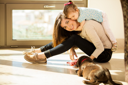 Beautiful young Hispanic mother with a baby girl and a cute Labrador puppy at home photo
