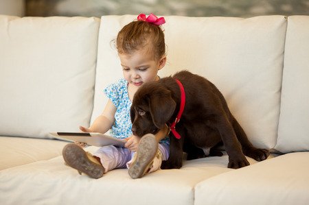 couches: Beautiful little girl playing with a tablet computer while her dog stays by her side