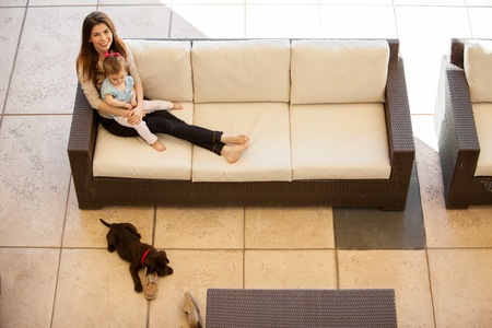 Cute young mother relaxing with her baby girl and her dog on a patio