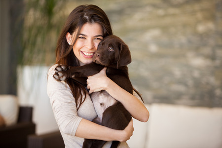 Beautiful young woman hugging and showing some love to his puppy at home Imagens