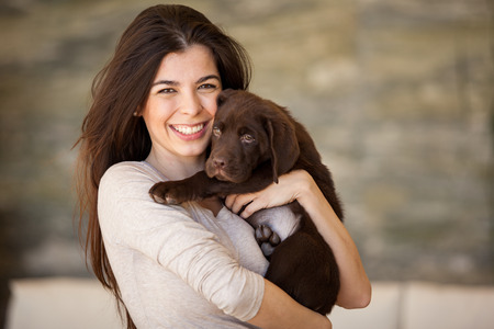 Portrait of a happy young woman holding her cute brown Labrador at home photo