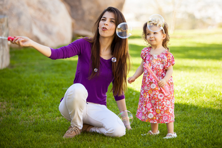 Beautiful young Hispanic mother and her baby girl having fun with bubbles outdoors photo