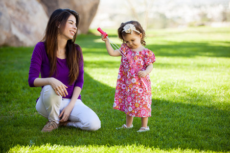 Pretty baby girl and her young mom trying to make some bubbles at the park photo