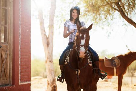 horseback riding: Beautiful Hispanic woman riding a horse and smiling Stock Photo