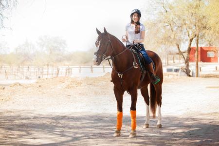 복사 공간의 맑은 날 많음에 말을 타고 헬멧에 젊은 여자의 전체 길이 샷