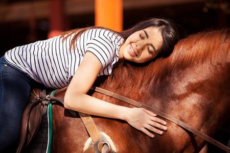 horseback: Pretty Hispanic brunette giving her horse a hug while riding him outdoors