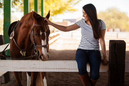 Pretty Hispanic young woman petting and having fun with a horse in a ranch