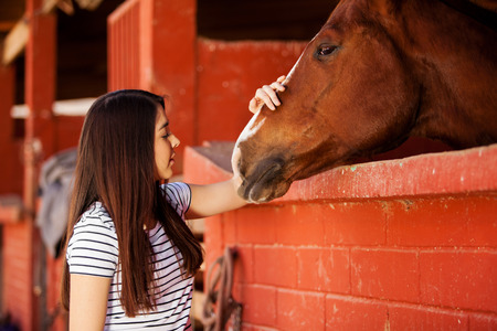 Portrait of a beautiful Hispanic woman touching and spending time with her horse