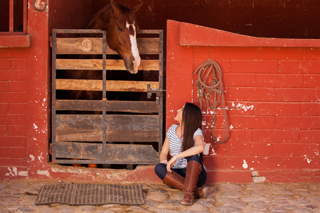 horse stable: Young Hispanic woman keeping some company to her horse in a stable Stock Photo