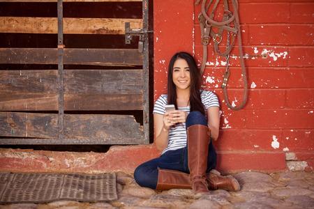 parapente: Mujer joven feliz mensajes de texto, mientras que pasar algún tiempo en un establo