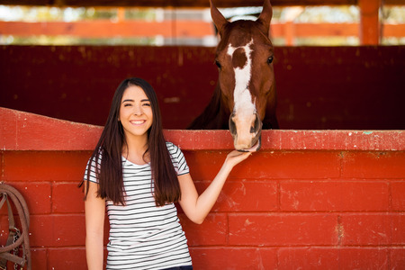 Portrait of a stunning young woman hanging out with her horse and smiling
